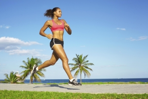 Sporty mixed race woman jogging. Color image, copy space, african american ethnicity female running with green grass and blue sky.