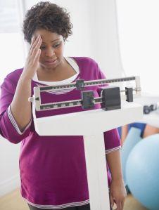African American woman weighing herself
