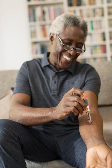 Smiling senior man taking insulin