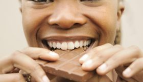 Woman biting into a chocolate slab