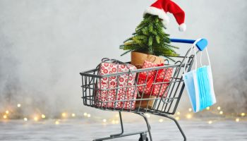 Christmas Shopping and COVID-19. Shopping Cart with Protective Face Mask and Gifts