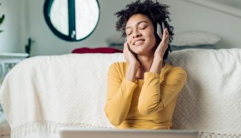 Portrait of a beautiful Afro woman enjoying music at her bedroom